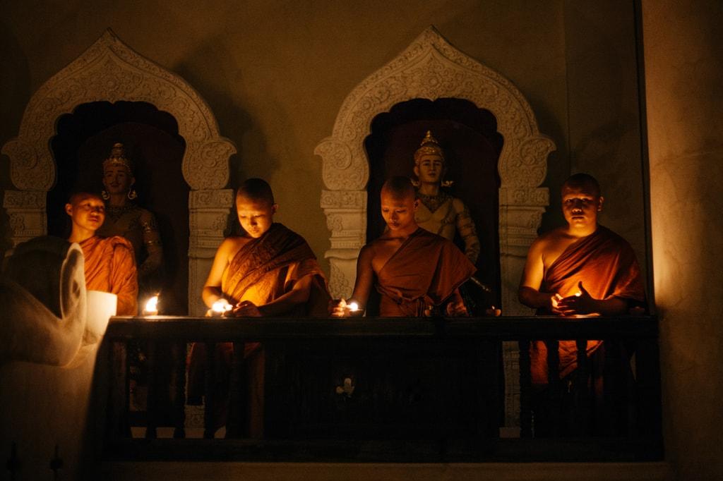 Four monks light candles outside a temple | Gioia Emidi / © Culture Trip