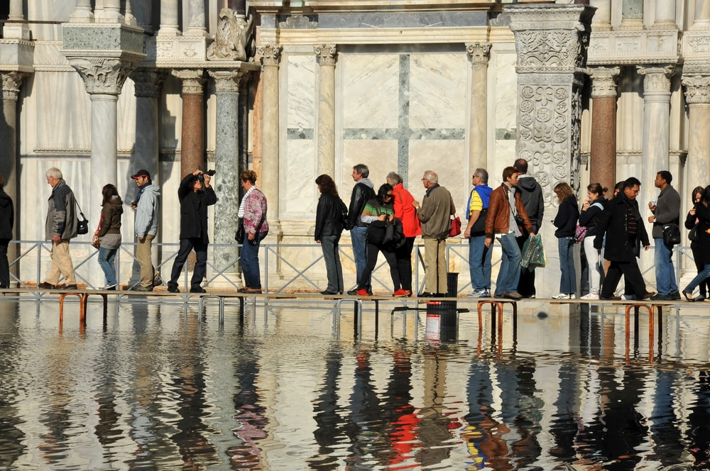 Visitors to Venice walk on duck boards as sea water floods St. Mark's Square, Venice in 2010 | Mountainpix/Shutterstock