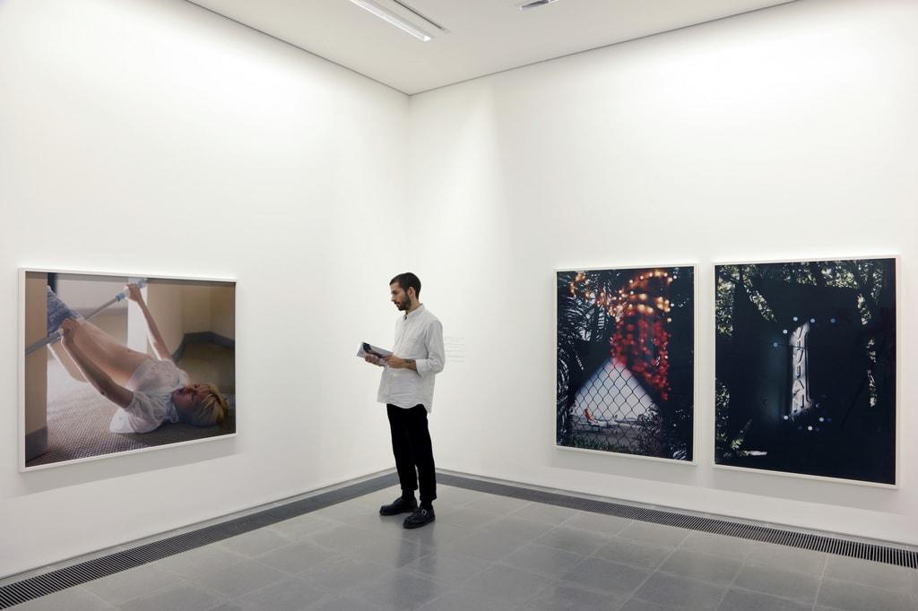 Gallery visitor looking at photographs by Torbjørn Rødland at Serpentine Sackler Gallery