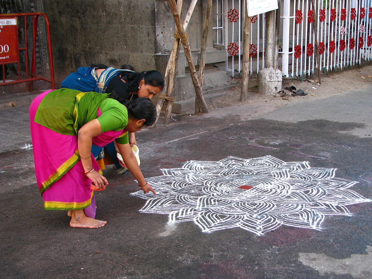 1280px-India_-_Sights_&_Culture_-_Women_drawing_an_intricate_kolam_outside_the_Mylapore_Temple_(2278407131)