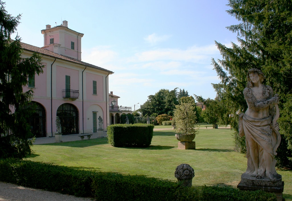 A pink building and green lawn, with bushes, hedges, trees and a classical statue, in the Milanese region of Oltrepò Pavese