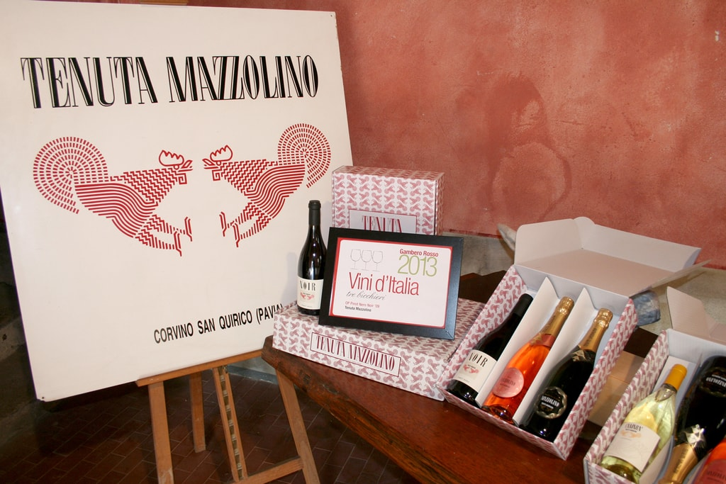 A table with a selection of different wine bottles produced in Oltrepò Pavese. There is a large poster with the words Tenuta Mazzolino beside the table and a red wall in the background.