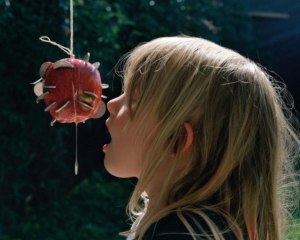 Photograph by Torbjørn Rødland of a girl going to eat an apple with coins in
