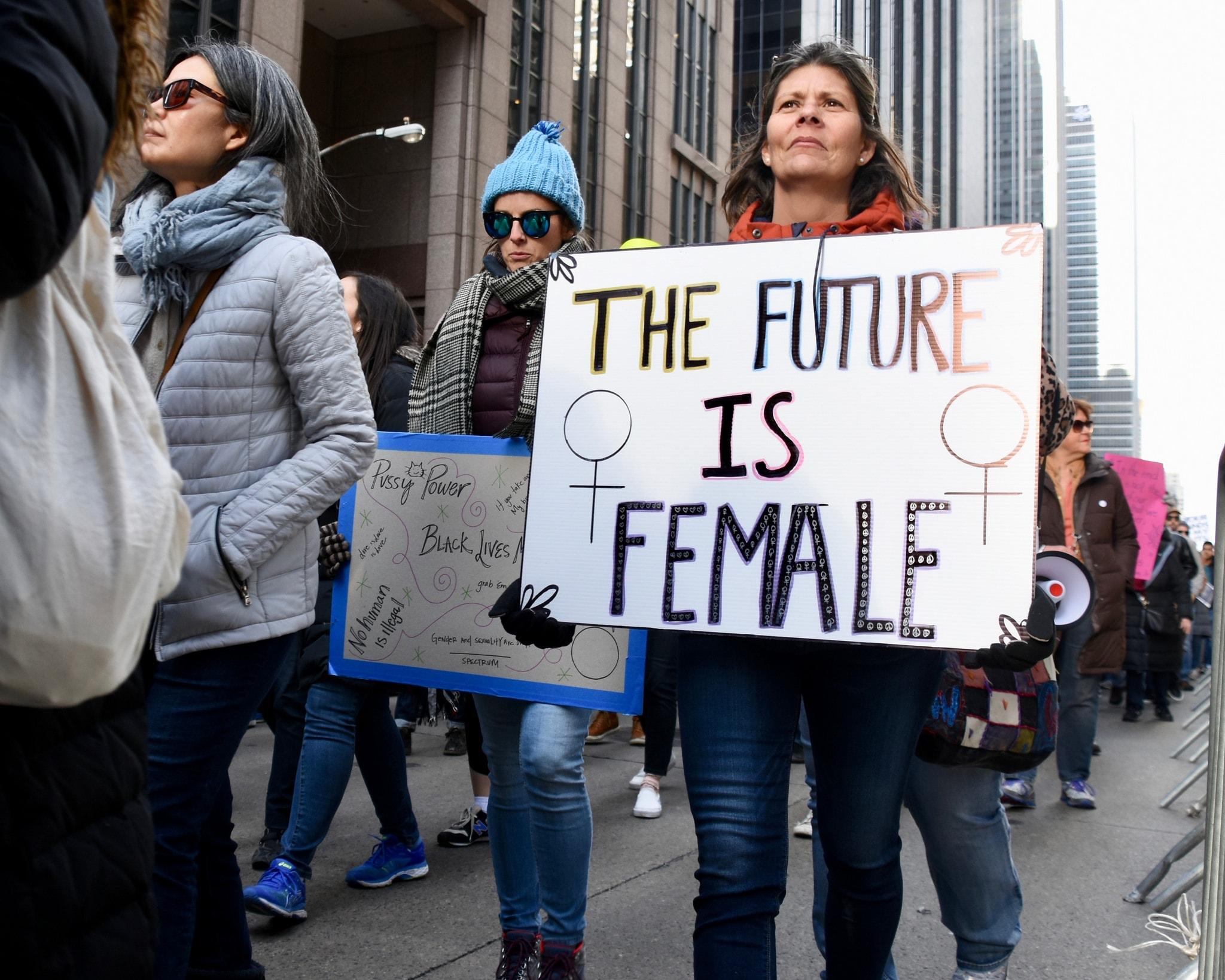 "A protester holds up a sign at the Women's March 2018 in NYC | <a href=""https://www.flickr.com/photos/alecperkins/28040475339/in/photolist-FwNcgb-E1Du82-23BSvfL-E1DtQi-23BSy2C-FwNbZE-23EF6G6-JHQMDM-JHQMVi-JHQN7a-22ieqUz-FwNcw1-23BStUj-23BSymA-23BSxxG-JHQNgt-JHQLpn-JHQLia-FwNbyE-23BSvnj-23BSu5E-E1Dvrp-23BSyXq-23BSvPw-E1DupV-JHQMMH-23BSwQ9-23BSvrs-23BStvo-E1Dv8P-23BStjw-JHQLtF-22ierbM-JHQMaR-23EF6wr-23BSuPW-23BStNh-23BSuGG-22ieqMk-E1DuZH-23BSue7-JHQLB6-22ier2P-JHQMrc-FwNbMA-23BSyhh-E1DvQF-23BSwj9-22ieqJp-23BSAXh"" target=""_blank"" rel=""noopener"">© Alec Perkins/Flickr</a>"