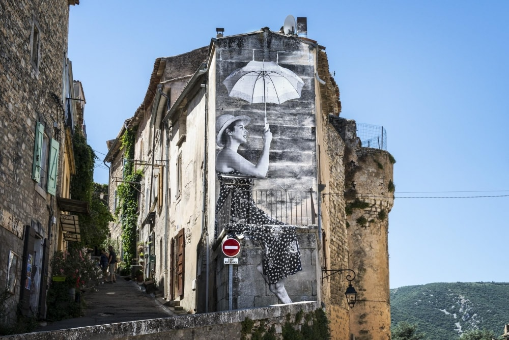 Agnès Varda and JR's image of the lady with the parasol, photographed in the South of France, in <em>Faces Places</em> | © Cohen Media