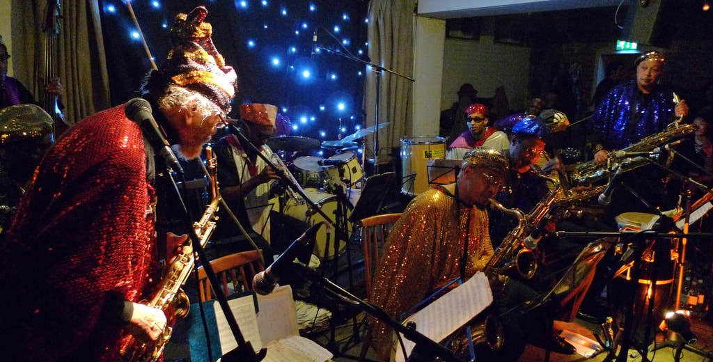 "The Sun Ra Arkestra | <a href=""https://www.flickr.com/photos/jazztourist/4540507541/in/photolist-7VehGM-7VegVR-7VhAnw-7VhAGf-7VhCqs-7VhxDd-7Vej78-7VeiWV-7VekPc-7Vhxvm-7VhyAE-7Vem7D-7VhBMA-7VemHT-7VhwGq-7VhyFo-a39aYJ-7VemUB-7VenEi-7VhBFd-7VhzkY-7VhxMf-7Venwz-7Veh8R-4scWhu-5PE8xP-7VhyQj-7VekBv-7VhBuE-9S49hp-7VhAVE-7VhxSL-7Vek98-4s8Tip-4s8Tj8-4scWkf-4s8T7T-4s8T46-5RrgV-4s8TnB-4s8Tfr-4scWuJ-4scWob-5wnakn-4s8TdM-4s8Tmx-4scWpE-4scWwY-4s8T2M-5Rrai"" target=""_blank"" rel=""noopener"">© Andy Newcombe/Flickr</a>"