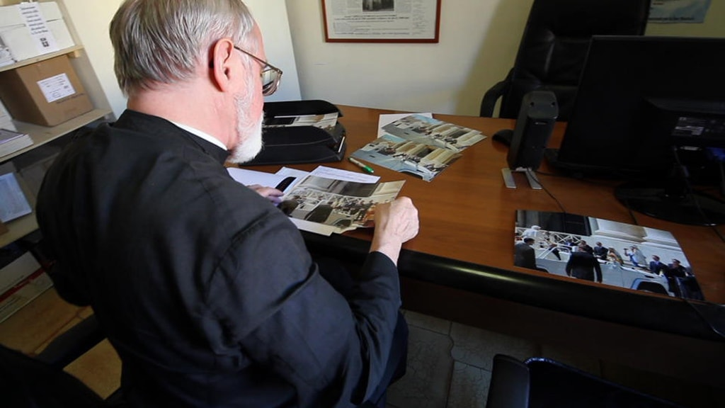 Father Gruner Photos at Office - Still from film Img 1