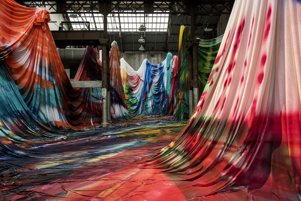 German painter Katharina Grosse creates an immersive installation out of colourfully painted fabric at Carriageworks in Sydney