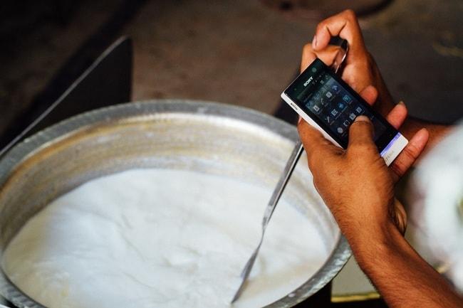 Checking Smartphone While Making Yogurt