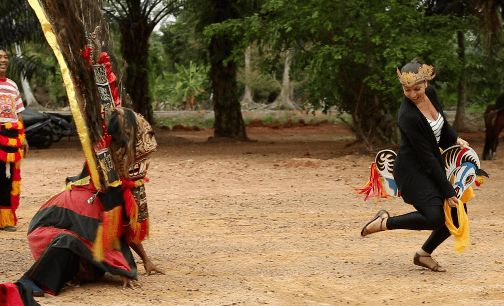Mickela Mallozzi dances the Horse Dance with an Indonesian family Malaysia - Photo by Nick Nichols