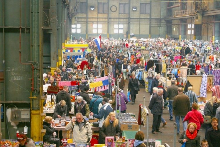 People shop at the indoor secondhand and vintage flea market in the IJ Hallen, Amsterdam