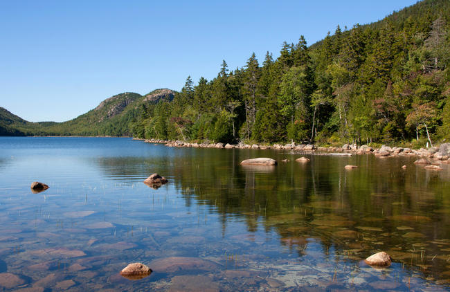 Acadia National Park, ME ? September 8, 2014: A line of trees is reflected in the clear waters of Jordan Pond, with the Bubbles
