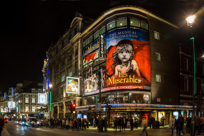 London's West End at night with Les Miserables at Queens Theatre in Shaftesbury Avenue.