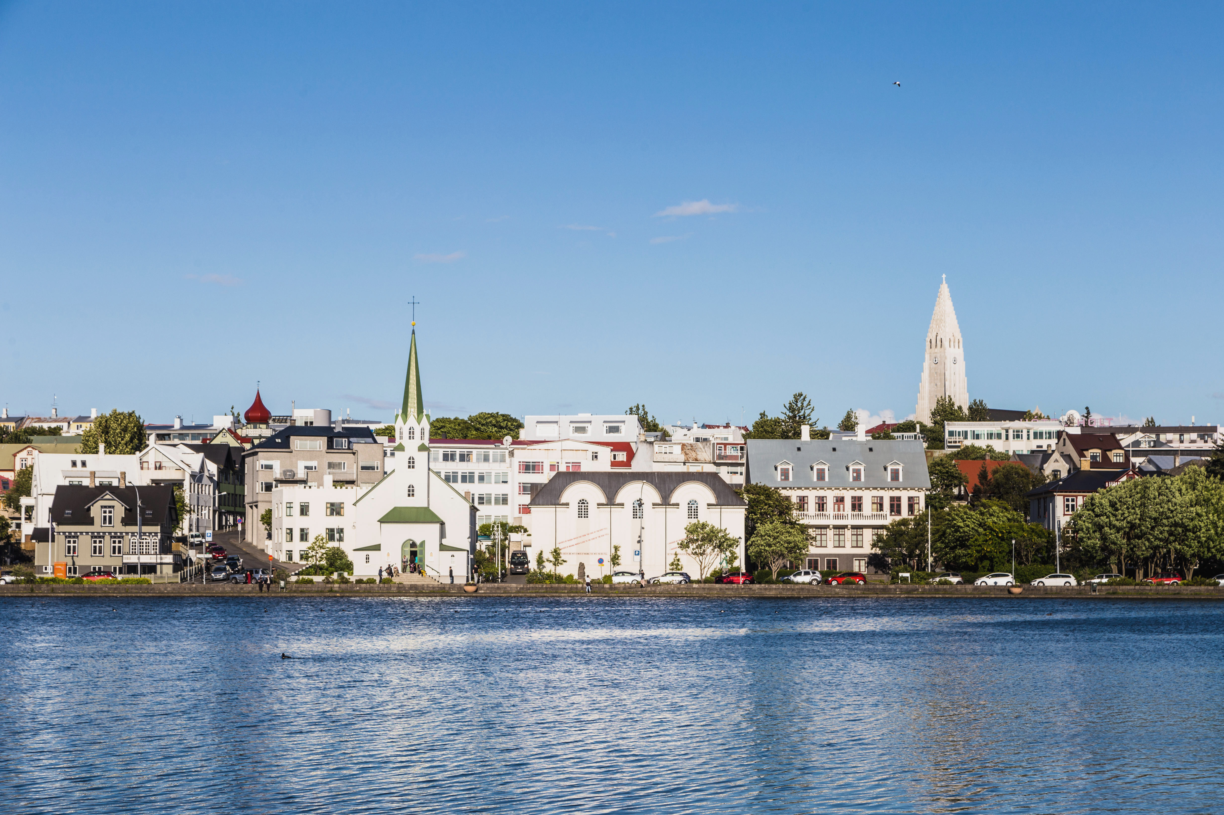 Reykjavik cityscape, with the bell tower of the Hallgrimskirkja church, viewed from across the Tjornin lake in the heart of Iceland capital city on a