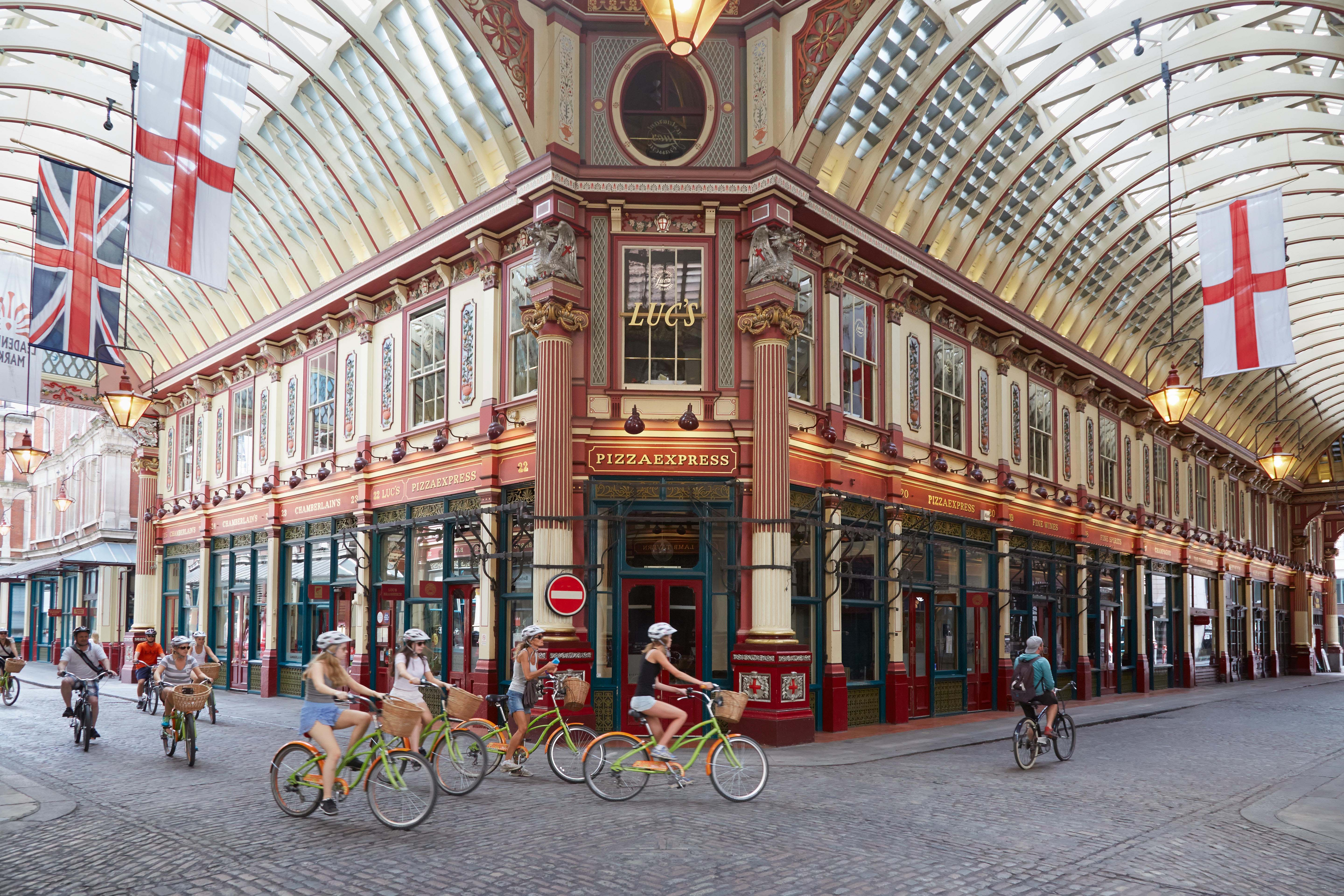 Leadenhall covered market interior with tourists in bicycle in a summer afternoon in London