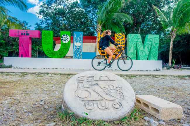 TULUM, MEXICO - JANUARY 10, 2018: Outdoor view of unidentified woman biking next to huge colorful letters Tulum at the enter of Mayan Ruins of Tulum in Meixco