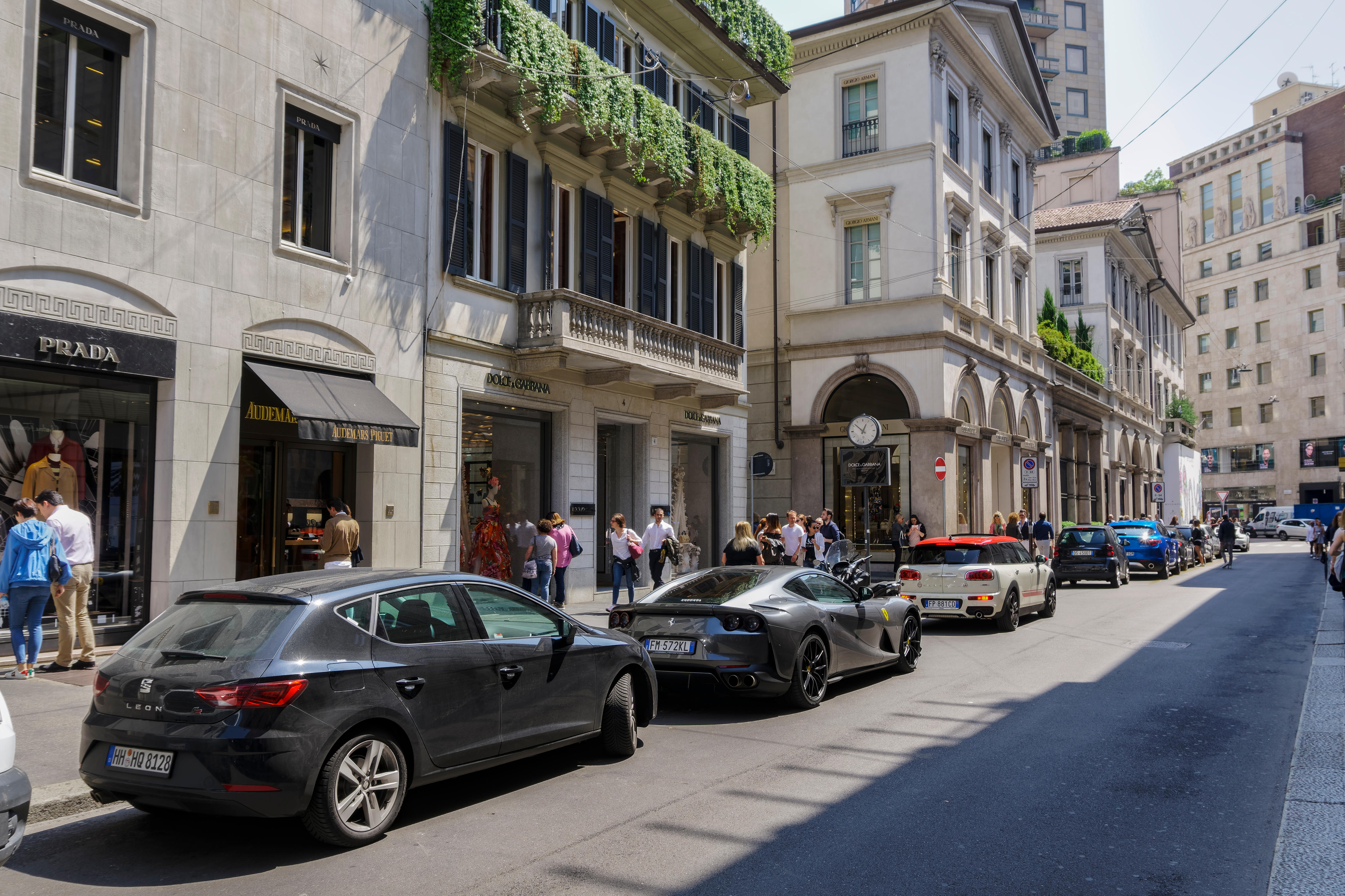 Milan Via Monte Napoleone upscale shopping street with luxury cars. People outside Milano fashion district Dolce & Gabbana high end exclusive boutique