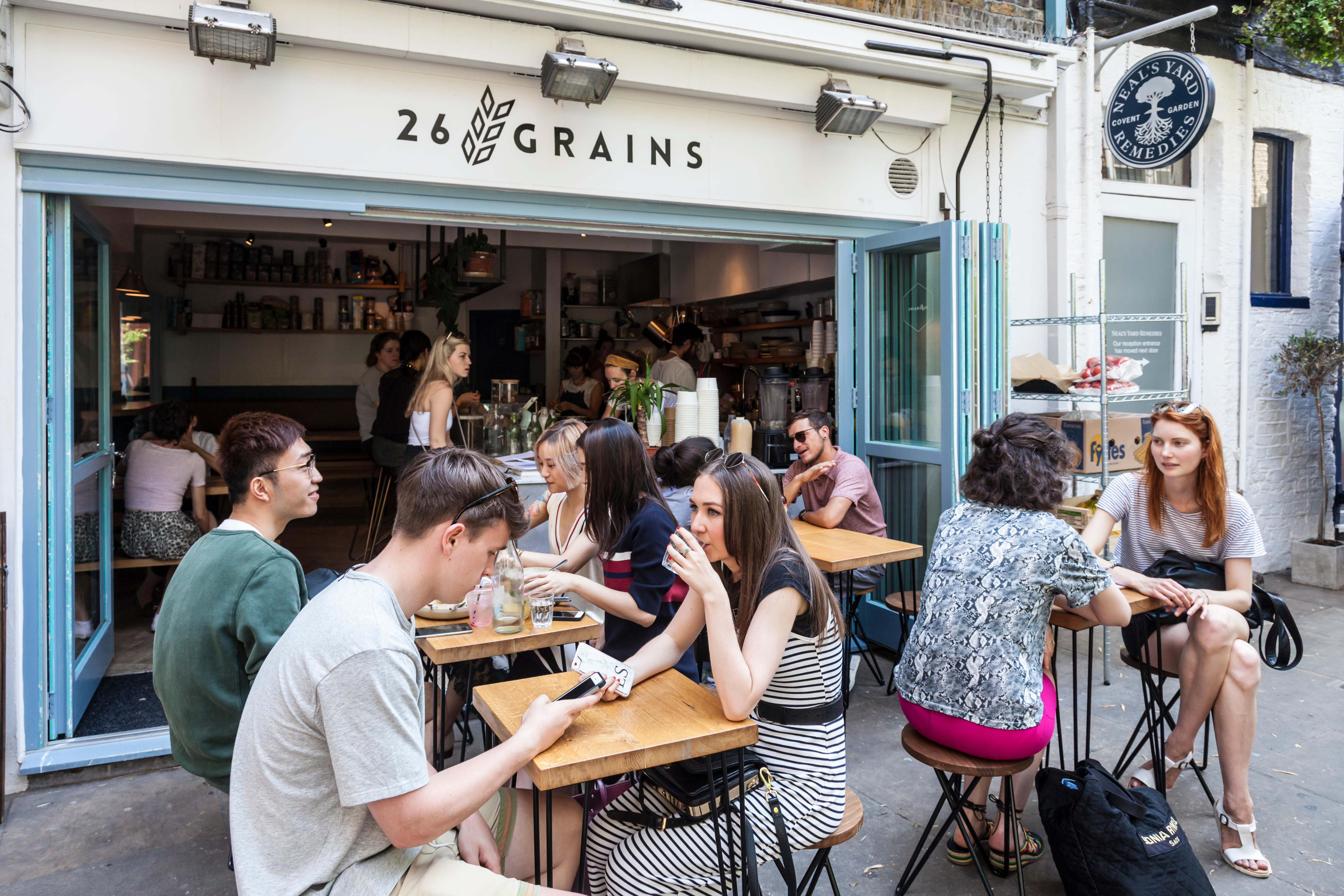 Clients sitting, relaxing, chatting, drinking in Neal's Yard courtyard, outside 26 Grains restaurant. Seven Dials, London, England, UK